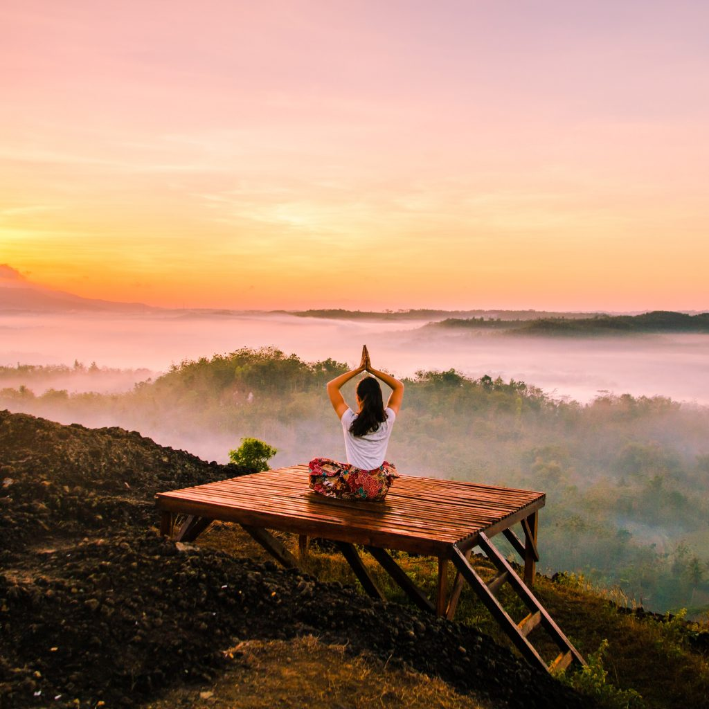 woman in a white top doing yoga at sunrise